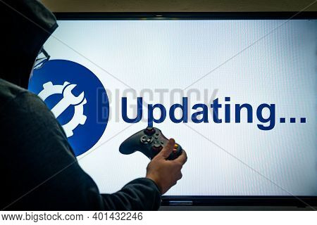 Hooded Man Holding A Gaming Controller In Front Of A Screen Showing An Updating Message For A Game O