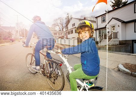 Portrait Of A Little Boy Ride On A Tow Tandem Bike Attached To Father On Urban Street View From Behi