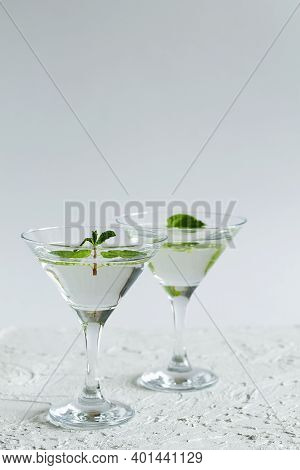 Cocktail In The Bar. Two Martini Glasses Of Cocktail With Green Mint On White Background. Alcohol Dr