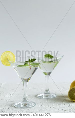 Margarita Cocktail In The Bar. Two Martini Glasses Of Cocktail With Green Mint And Lime On White Bac