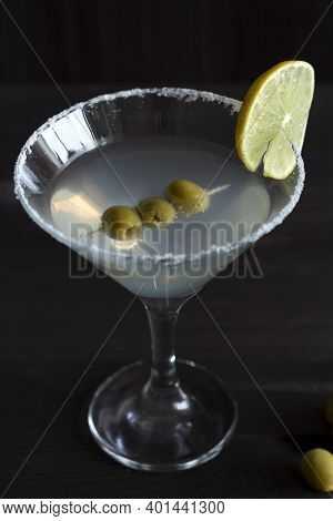 Close-up Margarita Cocktail In The Bar. Martini Glass Of Cocktail With Olives On Wooden Background.