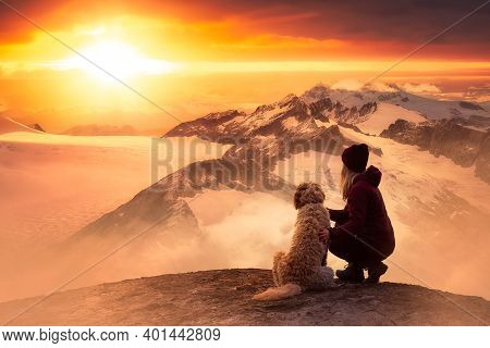 Adventurous Girl Is Hiking With A Dog On Top Of Rocky Mountain With Canadian Nature Landscape From B