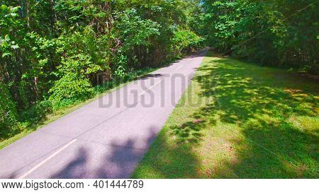 Paulding County, Ga Usa - 06 11 20: Paved Trail Side Ahead View And Green Foliage In The Summer Silv