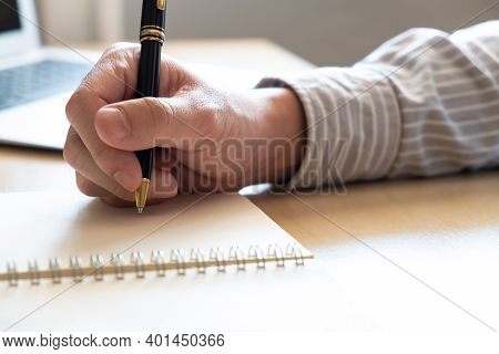 Selective Focus At Human Hand Using Pen To Write Down Short Note On Paper On Working Table. With Blu