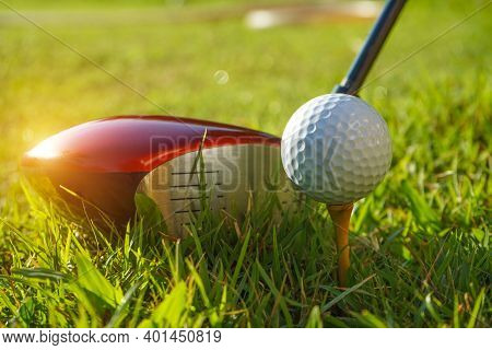 Golf Club And Ball On Tee In Grass. Golf Balls On The Golf Course With Golf Clubs Ready For The Firs