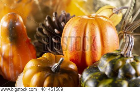 Small Orange Pumpkins, Orange Squash, Pinecones, And Green Squash With A Golden Background