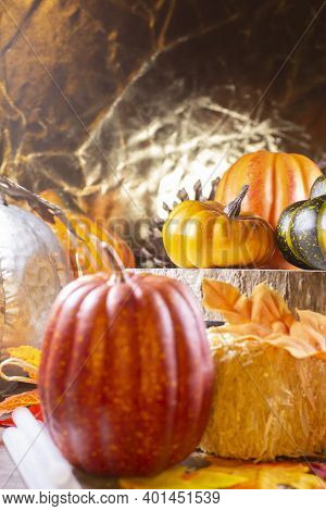 Small Red Pumpkin Next To Hay Covered With Leaves, Orange Pumpkins, Orange Squash, And A Green Squas