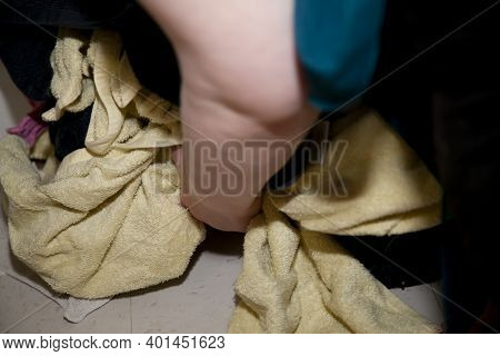 Woman Lifting Dirty Yellow And Black Towels  And Colorful Wash Cloths Off The Floor
