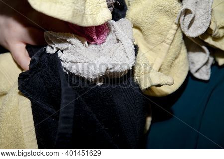 Woman Carrying Dirty Yellow And Black Towels With Other Colorful Wash Cloths To Do Laundry