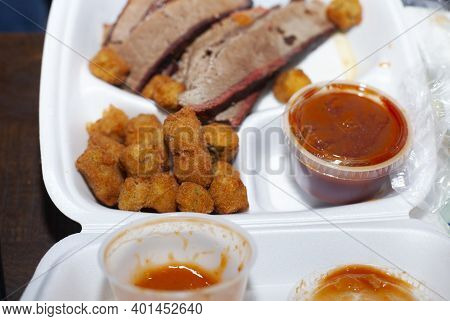 Close Up Of A Brisket Meal, Including Fried Okra And Baked Beans, In A White Takeout Box