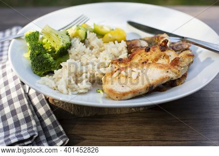Sliced Chicken Breast, White Rice, Grilled Vegetables: Brocoli, Zucchini And Squash On A White Plate