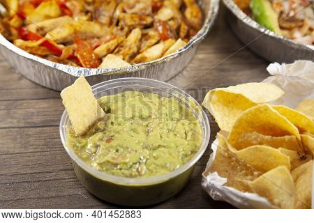 Tortilla Chip In Guacamole Next To An Open Bag Of Chips And Two Takeout Meals In Tin