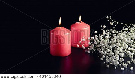 Red Burning Candles, White Flowers On Black Background. The Concept Of Mourning, Sorrow And Sadness.