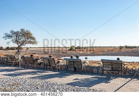Etosha National Park, Namibia - June 12, 2012: Tourists At The Waterhole Viewpoint At Okaukeujo Rest