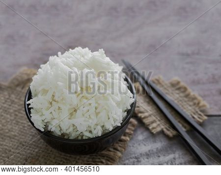 Jasmine Rice White Organic In Black Cup And Black Chopsticks On Hemp Sack With Blur Image Of Ear Of