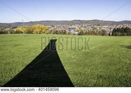 Black Shadow Of A Tower On The Green Field Near The Town