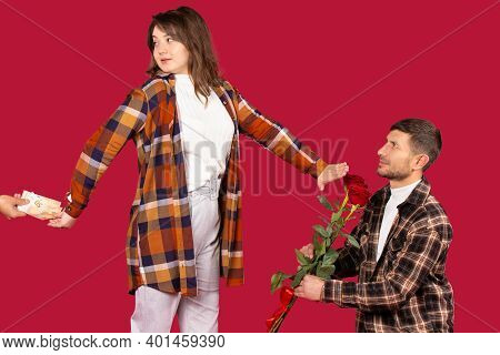 Young Couple On A Red Background. The Woman Refuses Flowers And Gives Preference To Money.
