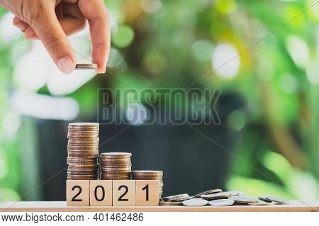 A Hand Putting The Coins On The Wooden Table Like A Growing Graph. With Text 2021, On Green Blurry B