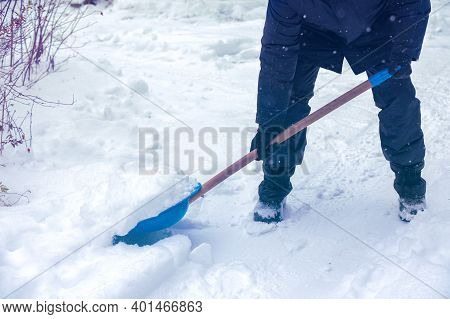 A Man With Snow Shovel Cleans A Road In Winter. The Man Shoveling The Snow After Snowfall