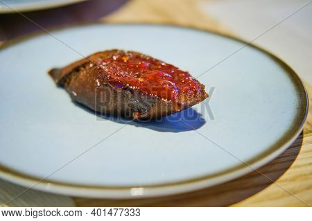 Croutons With Black Bread And Tomato Sauce On A White Plate, Close Up