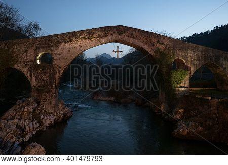 Illuminated Medieval Roman Hump-backed Stone Arch Bridge Over Sella River In Cangas De Onis At Twili