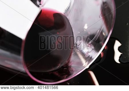Glass Of Red Dry Wine Spilled On Black Surface Close-up Macro Photography