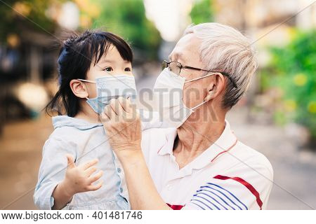 Family Grandfather And Granddaughter In Medical Mask. Senior Man And Child Girl Standing On Public R