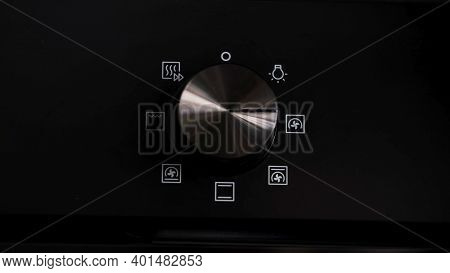 Turning The Cooktop Button On A Electrical Oven On. Concept . Close Up Of Woman Hand Turning The Han