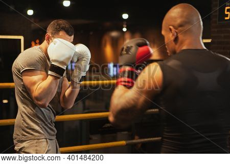 Two Male Boxers Sparring In Boxing Rink At The Gym. Athletic Young Boxing Fighters Training Together