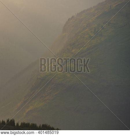 Hazy Light Over Slopes Of Mountains In Glacier National Park In Summer