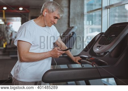 Senior Healthy Man Listening To Music On His Smart Phone, Preparing For Cardio Workout On A Treadmil