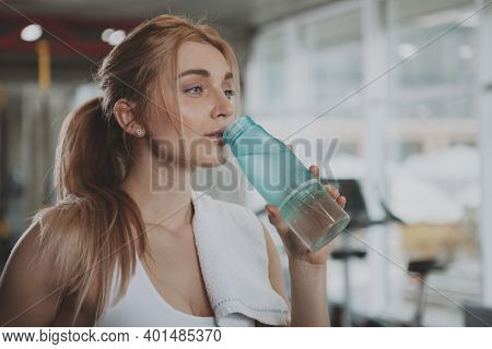 Close Up Of A Gorgeous Young Sportswoman Looking Away, Drinking Water After Exercising. Charming Hea