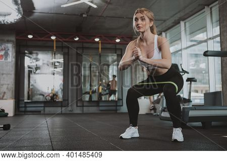 Full Length Shot Of A Beautiful Blond Sportswoman Doing Squats With Rubber Resistance Bans, Copy Spa
