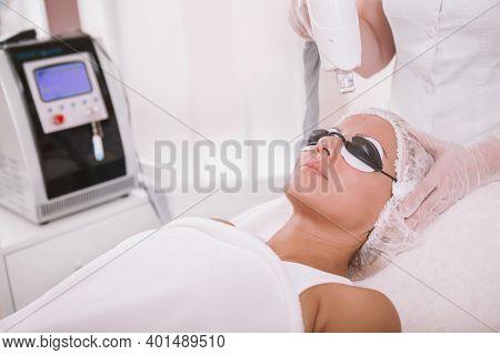 Mature Woman Getting Facial Laser Treatment. Professional Dermatologist Removing Skin Pigmentation O