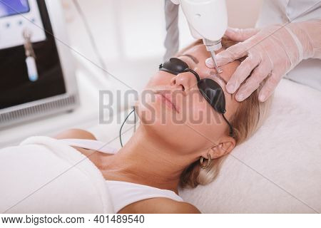 Close Up Of A Mature Woman  Getting Her Eyebrow Tattoo Removed At Cosmetology Clinic. Dermatologist