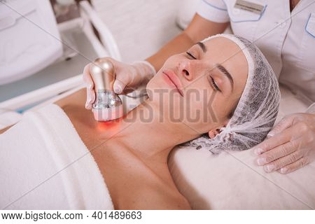 Attractive Woman Relaxing At Beauty Clinic, Getting Skin Tightening Treatment By Cosmetologist. Rf L