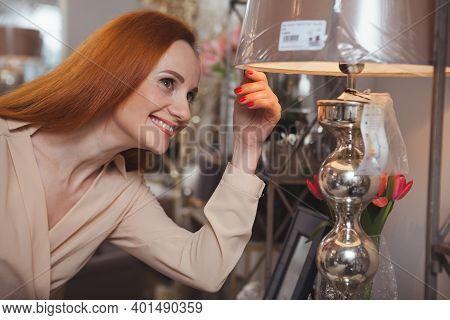 Charming Mature Woman Smiling Joyfully, Choosing New Lamp At Home Furnishings Store. Happy Female Cu