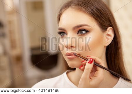 Close Up Of A Stunning Beautiful Young Woman Getting Professional Makeup. Makeup Artist Applying Lip