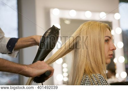 Cropped Profile Shot Of A Blond Haired Woman Having Her Hair Styled At Beauty Studio. Professional H