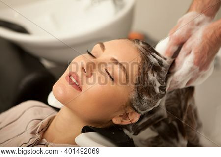 Close Up Of A Beautiful Young Woman Enjoying Head Massage With Her Eyes Closed, While Professional H