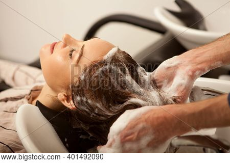 Cropped Shot Of A Woman Enjoying Hair Wash Treatment At Beauty Salon. Professional Hairdresser Washi