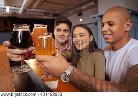 Diverse Group Of Friends Clinking Beer Glasses. Selective Focus On Beer Glasses In The Hands Of Youn