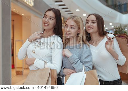 Group Of Beautiful Cheerful Female Friends Smiling, Looking At The Display Of A Store At Local Shopp