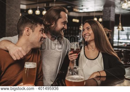 Happy Bearded Man Embracing His Friends, While Enjoying Drinking Beer At The Local Pub. Group Of Che