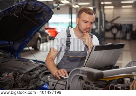 Mature Car Mechanic Looking Focused, Using Laptop While Repairing A Car At The Garage. Experienced A