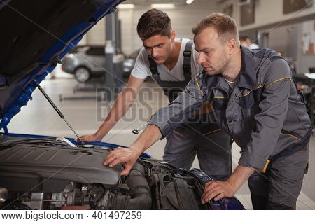 Mature Male Car Mechanic Helping His Younger Colleague Repairing Broken Automobile. Two Car Service