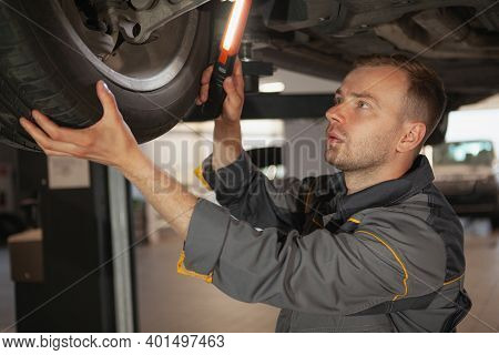 Mature Male Car Mechanic Looking Underneath A Car On The Lift, Using A Light. Experienced Auto Techn