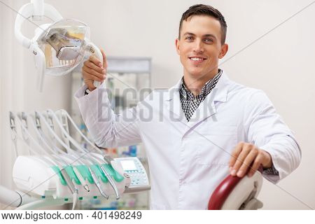 Happy Handsome Male Dentist Smiling Joyfully, Working At His Office, Copy Space. Professional Dentis