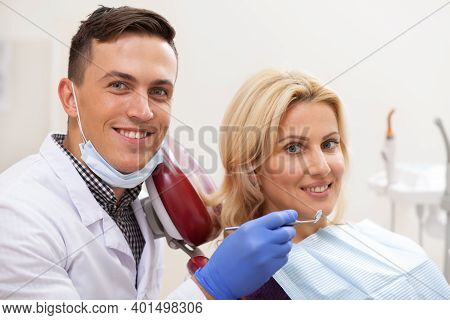 Happy Male Dentist And His Mature Female Patient Smiling Joyfully To The Camera After Dental Examina