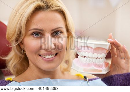 Close Up Of A Gorgeous Mature Woman Smiling Joyfully Holding Denture Mold, Posing At Dental Clinic.